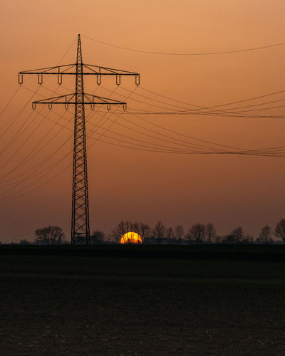 Silhouette electricity pylons on field against sky during sunset