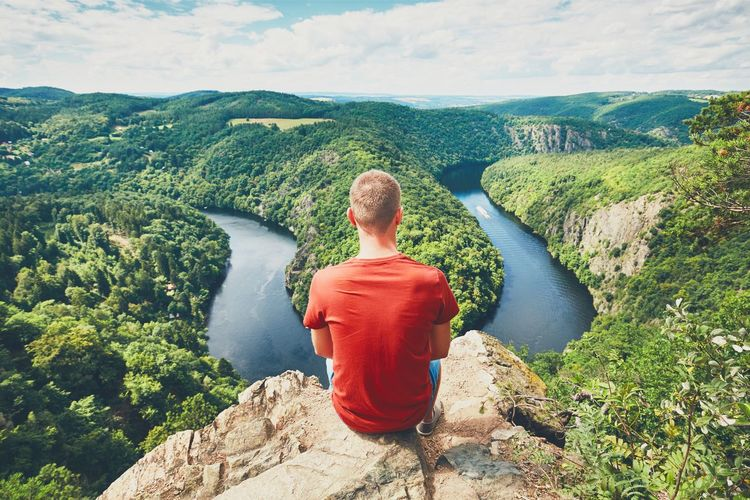 Rear view of man on hill against mountains and vltava river