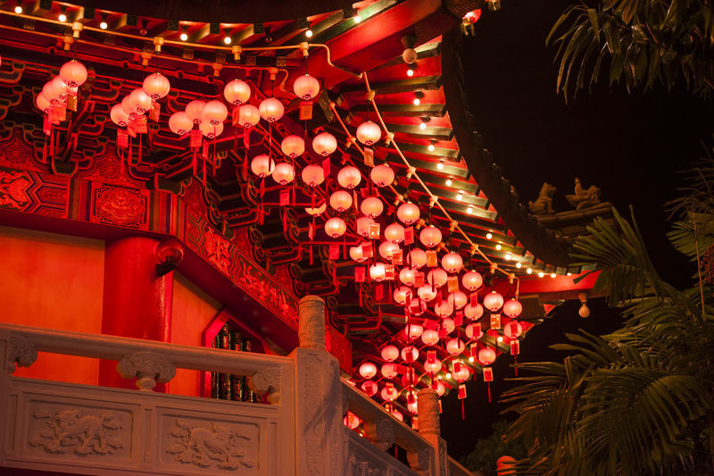 Low angle view of illuminated lanterns hanging in temple at night