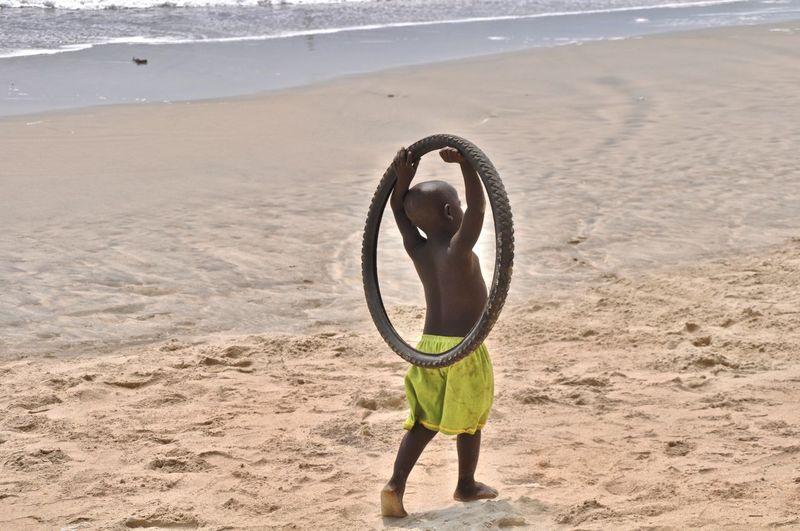 Rear view of boy holding wheel on beach