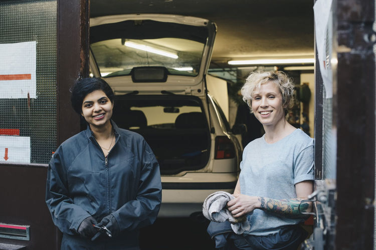 Portrait of female coworkers standing at entrance of auto repair shop