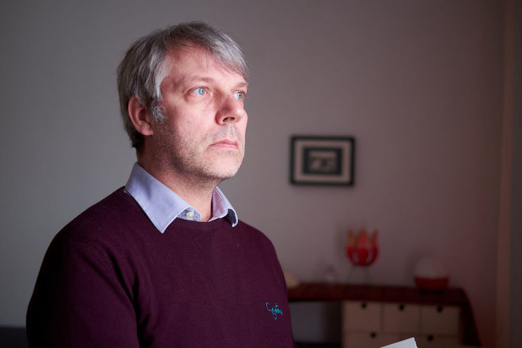 Portrait of mid adult man standing against wall at home