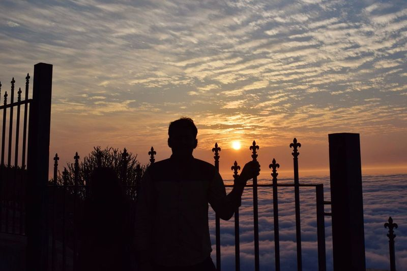 Silhouette Man Standing By Railing With Cloudscape Against Sky During Sunset