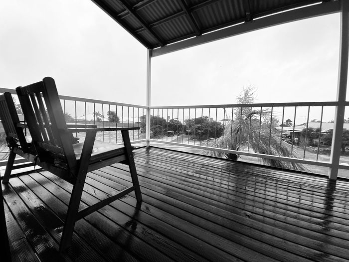 Empty chairs and tables against sky seen through balcony