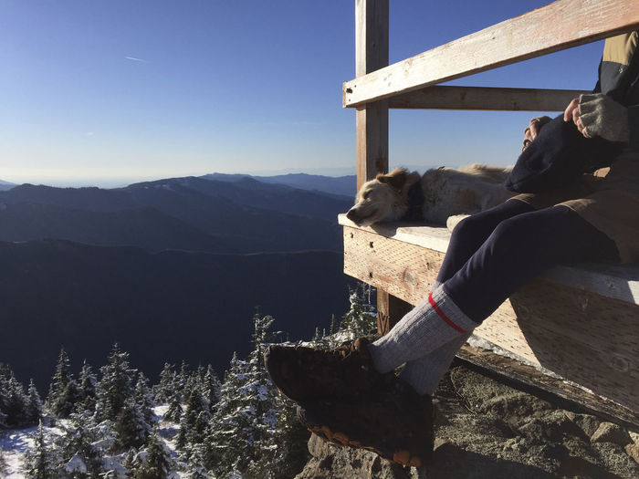 Man sitting on steps by mountains against sky