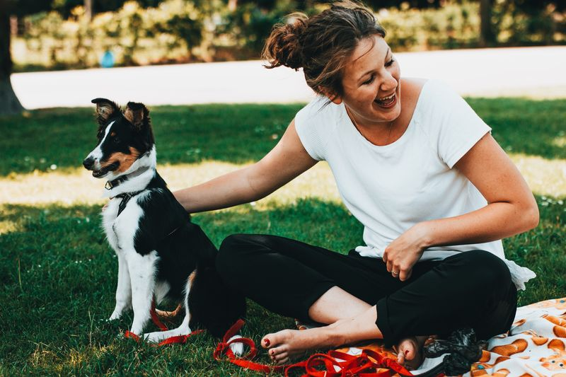 Happy young woman with dog sitting on field