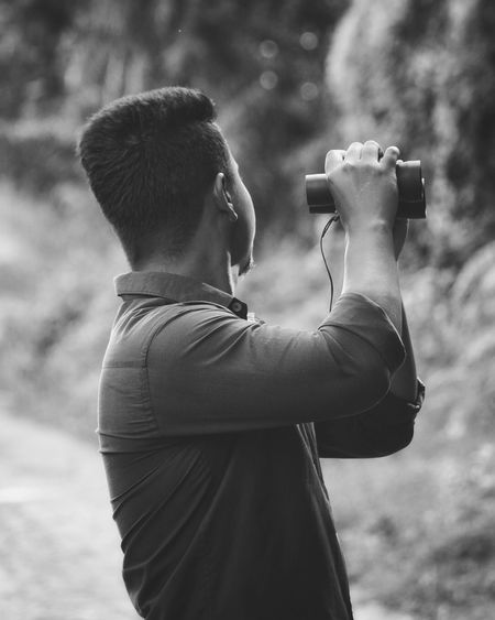 Side view of young man holding binoculars while standing outdoors