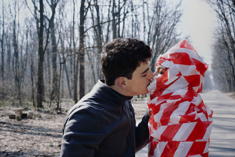 Side view of man kissing woman wrapped in cordon tape standing in forest