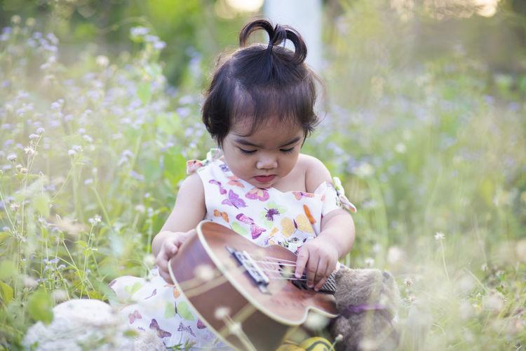 Cute girl sitting on field