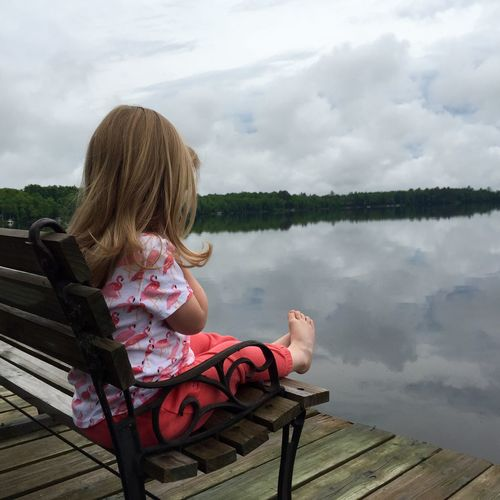 Girl Sitting On Bench At Pier By Lake Against Cloudy Sky