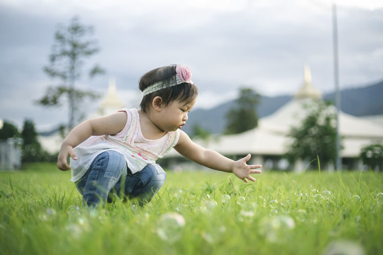 Girl crouching on grass against sky