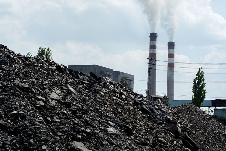 Air Pollution Architecture Building Exterior Built Structure Cloud - Sky Coal Coalmine Day Emitting Environment Environmental Damage Environmental Issues Factory Fuel And Power Generation Industry Low Angle View Nature No People Outdoors Pollution Sky Smoke - Physical Structure Smoke Stack