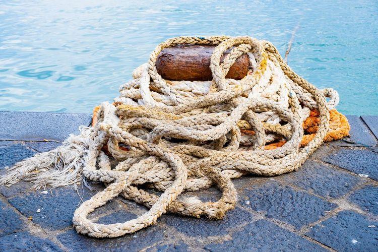Close-up of rope tied to bollard at harbor