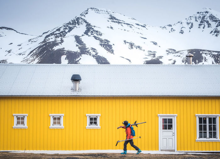 Full length of man on snowcapped field against sky during winter