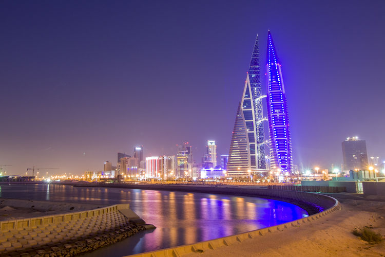 Manama Bahrain City Skyline at Night from King Faisal Highway with Bahrain World Trade Center as Background . Illuminated Skyscraper Cityscape Architecture Building Tower Modern Middle East Persian Gulf Arabic ASIA Islamic Travel Tourism Holiday Urban Skyline Building Exterior