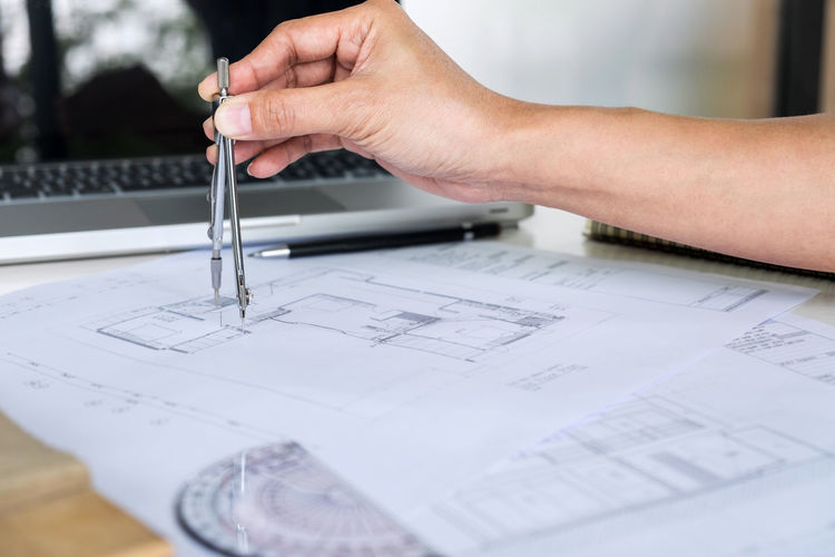 Close-up of architect holding drawing compass while working over blueprint