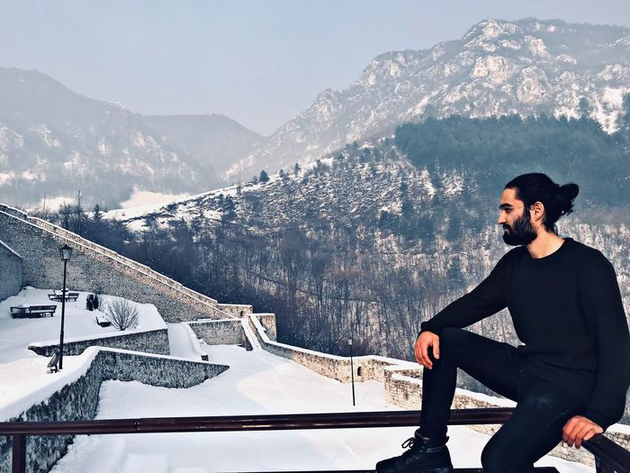 Young man sitting on railing against snowcapped mountains