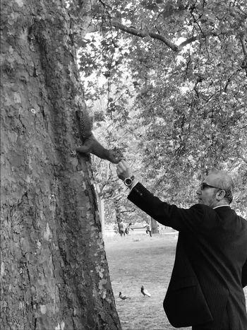 Tree One Person Arms Raised Outdoors Real People Day Human Arm Tree Trunk Leisure Activity Standing Human Body Part Branch Lifestyles Blackandwhite One Man Only Adult Only Men Human Hand Adults Only Squarrel Feeding  Closeupshot Bonding The Portraitist - 2017 EyeEm Awards