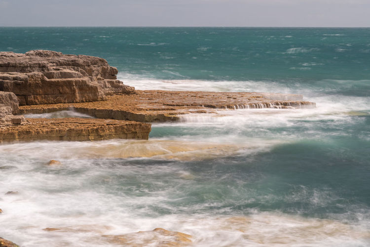 Long exposure of the tide flowing over rocks at portland bill in dorset