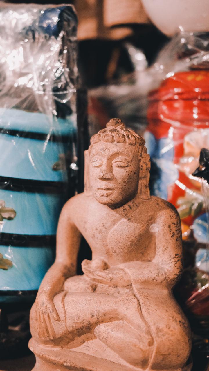 CLOSE-UP OF BUDDHA STATUE IN A SHOP