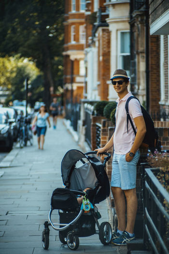 Man With Baby Carriage Standing On Street In City