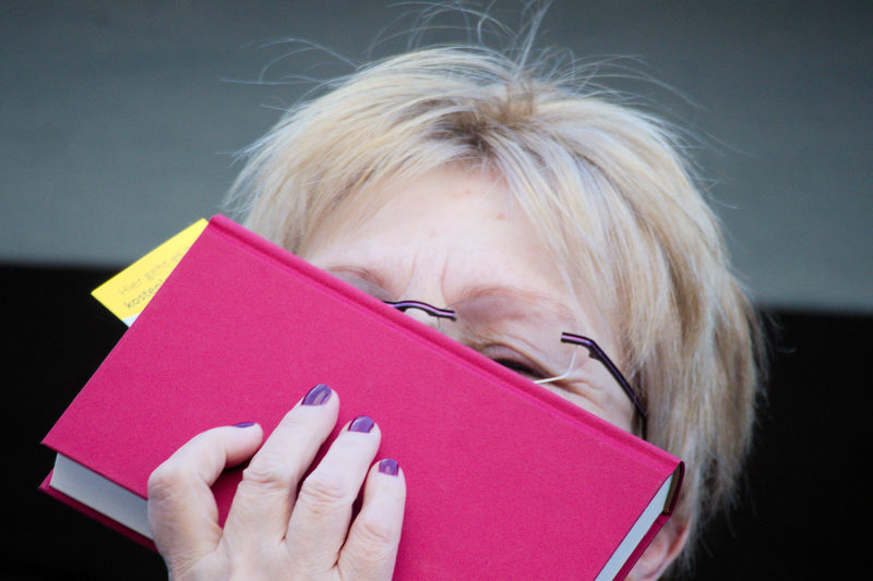 Close-up of senior woman covering face with book