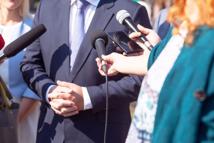 A politician or a businessman giving statement to the journalists. Media interview The Media Media Press Journalism Journalist Reporter Reporting Information Communication Public Relations Interview Media Interview Broadcasting Interviewing Gesturing Microphone Mic Publicimage Publicity Propaganda Politics Businessman Speaking Talking News