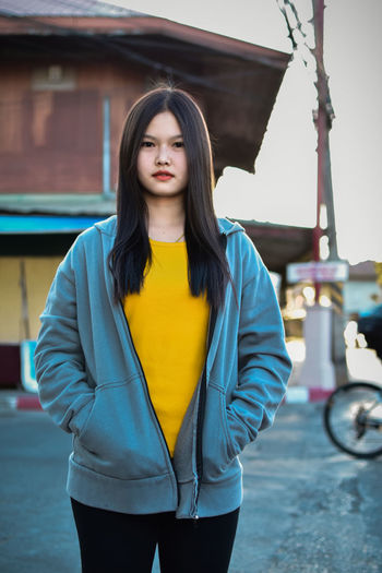 Portrait of beautiful young woman standing in city
