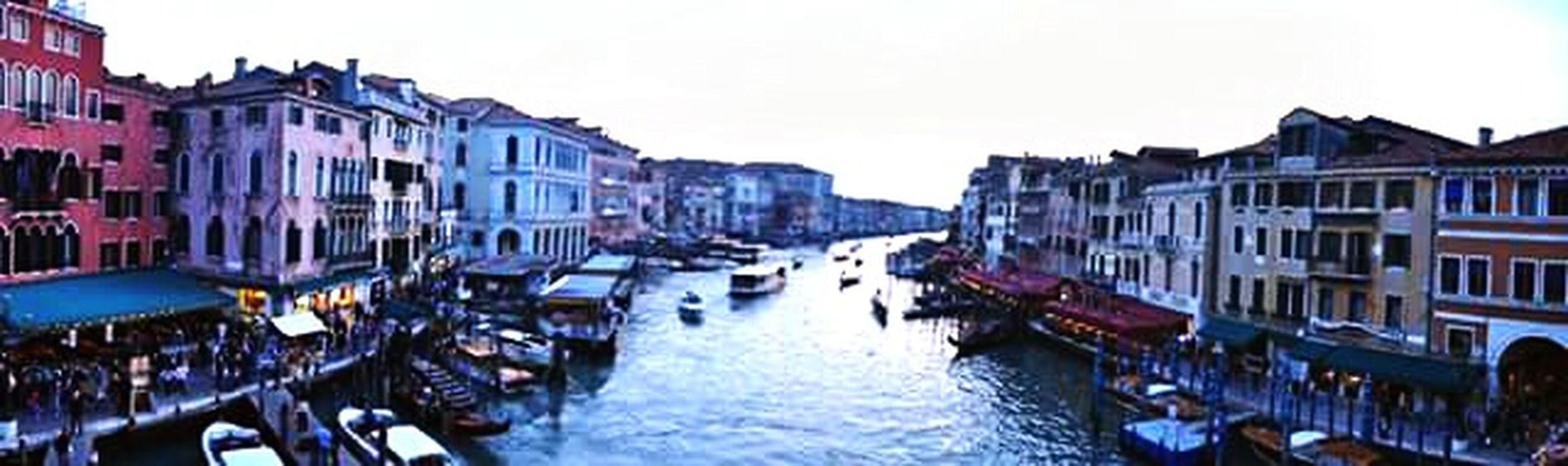 architecture, built structure, building exterior, canal, water, transportation, nautical vessel, mode of transport, boat, moored, waterfront, in a row, clear sky, residential structure, residential building, city, building, incidental people, diminishing perspective, day