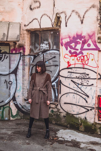 Full length of young woman standing against graffiti wall