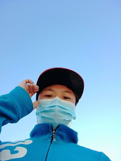 Portrait of boy wearing hat against clear blue sky