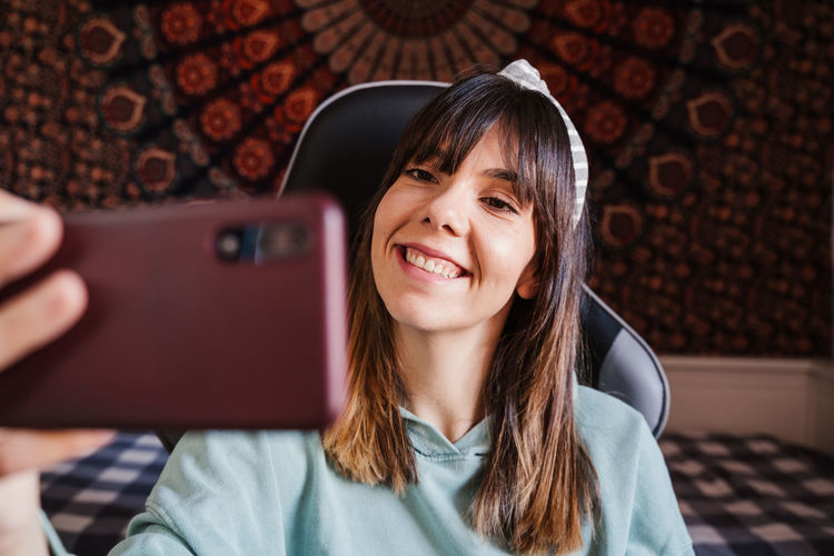 Smiling young woman taking selfie over mobile phone