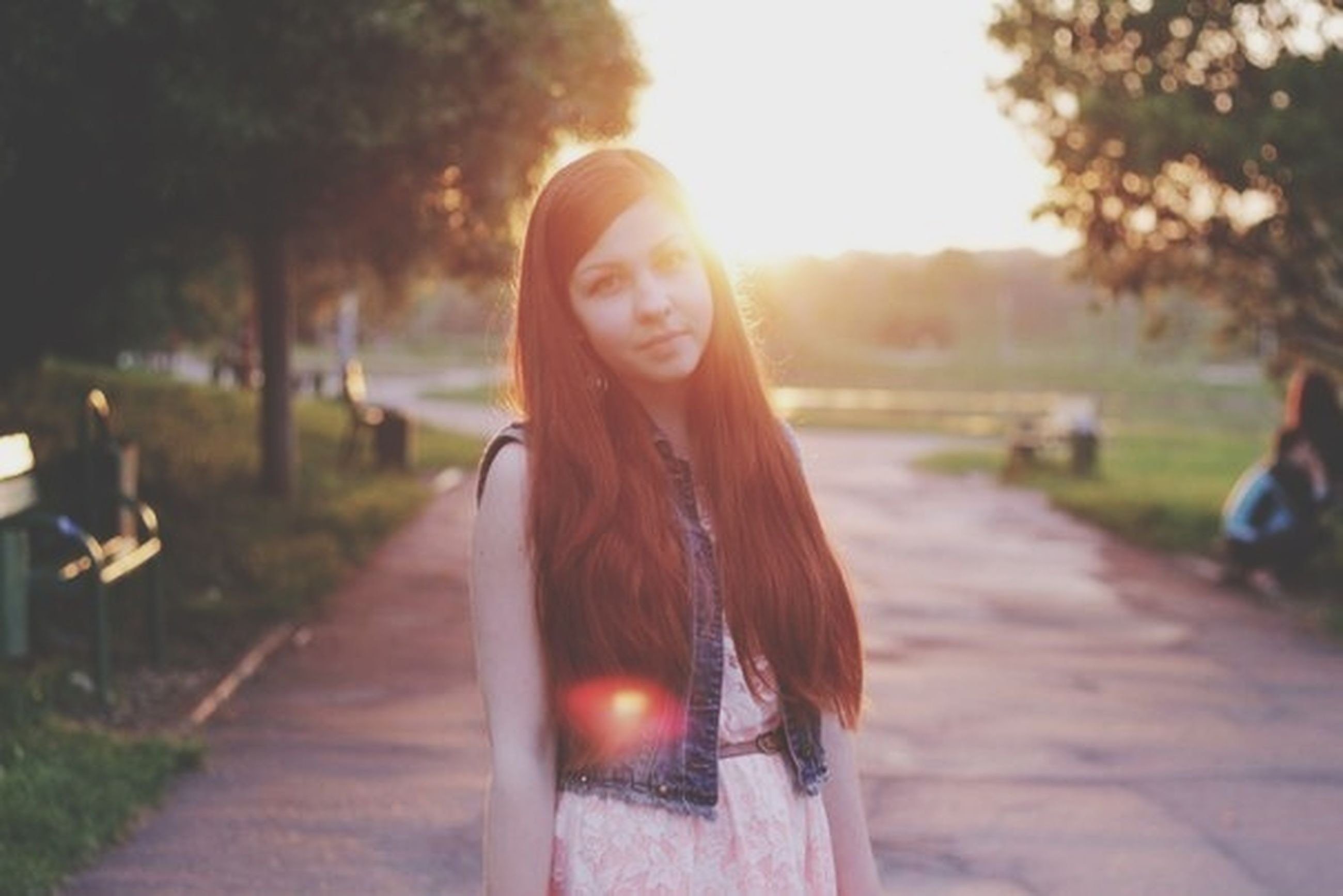 lifestyles, person, leisure activity, focus on foreground, tree, casual clothing, young adult, sunlight, long hair, young women, front view, portrait, looking at camera, standing, incidental people, park - man made space, outdoors, road