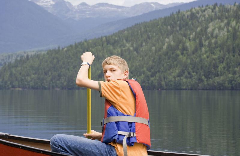 Portrait Of Teenage Boy Canoeing On Lake