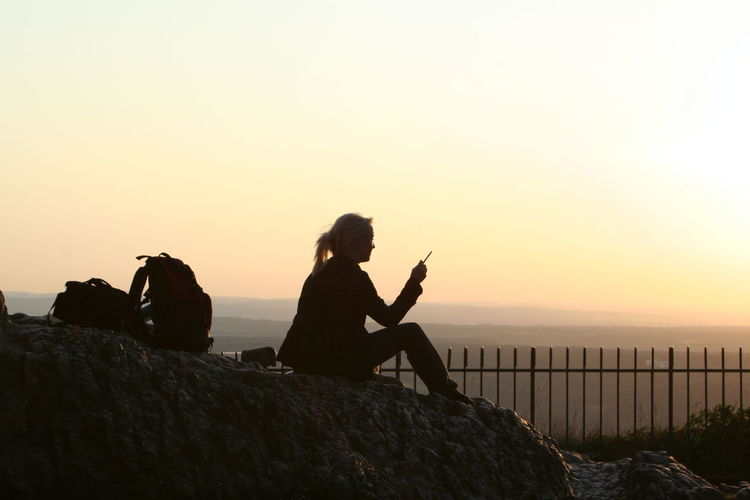 Silhouette woman smoking cigarette while sitting on rock at mountain against sky during sunset