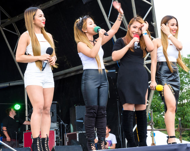 Fourth Impact on stage at the Barrios Fiesta in London. 4th Impact Barrio Fiesta Festival Filipino Filipinos Fourth Impact Group Leisure Activity Lifestyles Microphones Perfect Performance Singers Statue Women