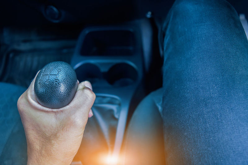 Midsection of man holding gearshift in car