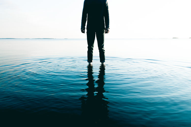 Low section of silhouette man standing in sea against clear sky