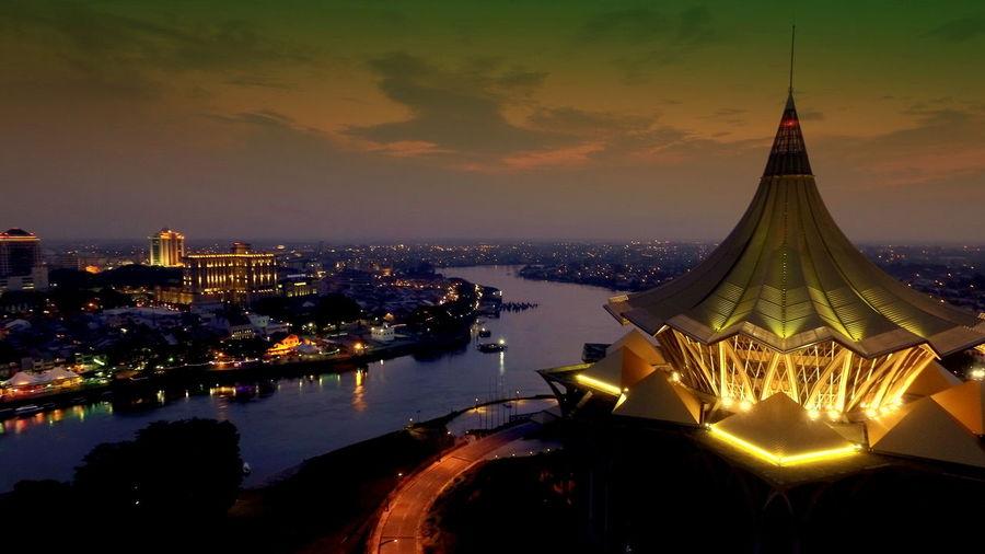 Illuminated sarawak state legislative assembly building by river at dusk