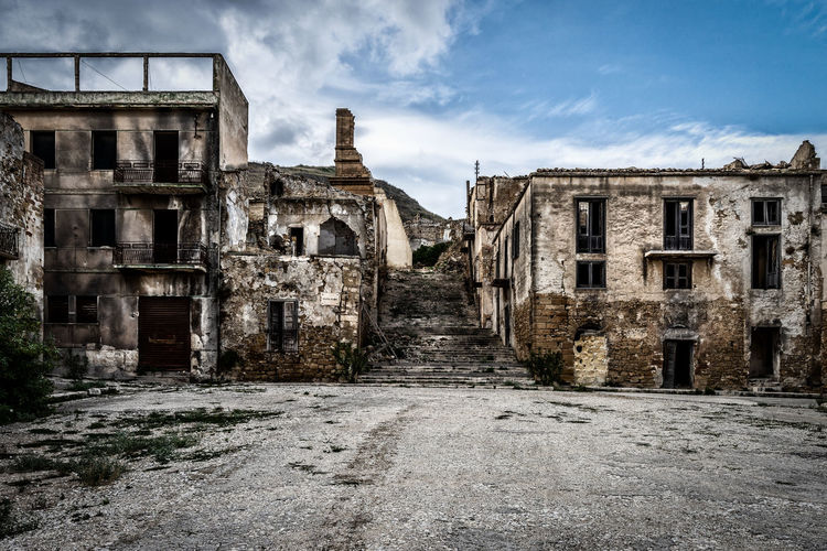 Abandoned Buildings Against Cloudy Sky