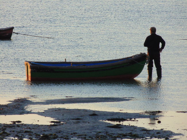 Man standing next to his wooden boat with lowtide in Alcochete, Portugal. Beach Beauty In Nature Day Full Length Gondola - Traditional Boat Men Mode Of Transport Moored Nature Nautical Vessel One Person Outdoors People Real People Sand Sea Standing Transportation Water Waterfront