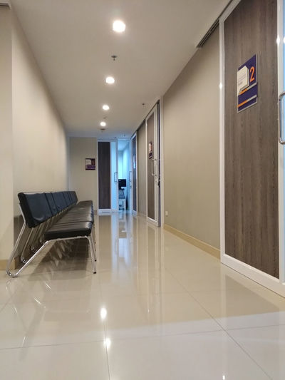 Empty chairs in waiting room in hospital. Indoors  Architecture Flooring Building Empty No People Corridor Arcade Absence Ceiling Illuminated Reflection Healthcare And Medicine Entrance Door Seat Wall - Building Feature Tiled Floor Built Structure Modern Waiting Hospital Room