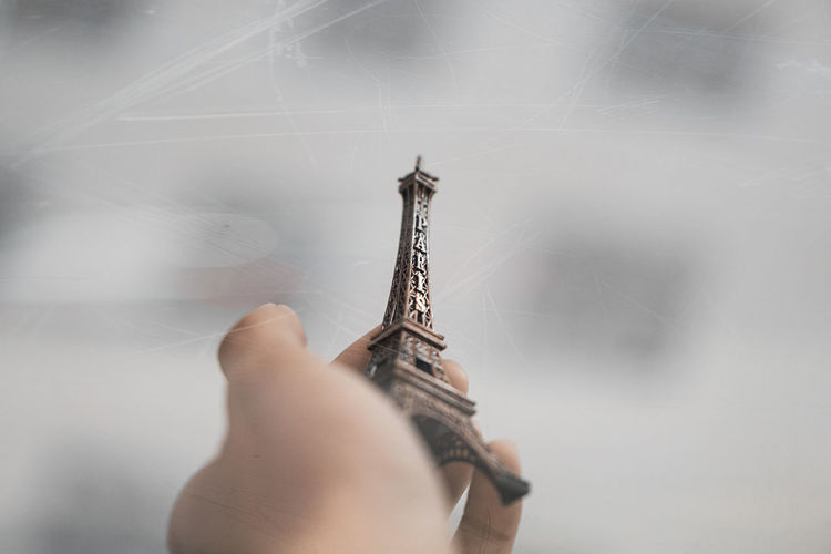 Cropped hand holding replica eiffel tower