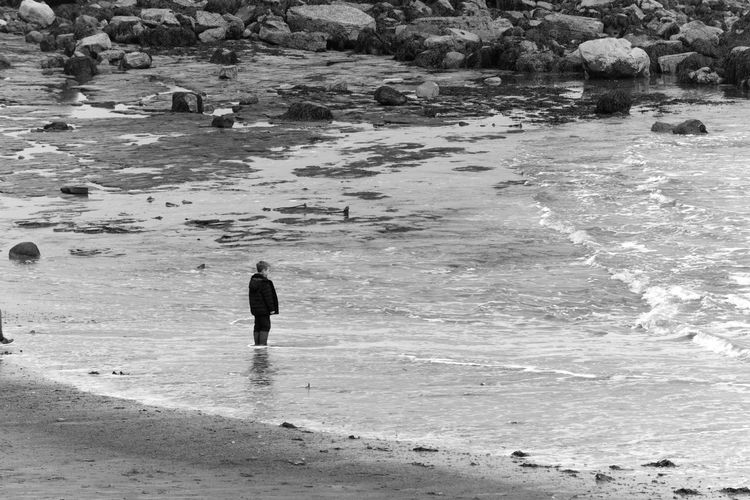 A day at the beach Outdoors Water Lifestyles Beach Land Sea Day One Person Rock - Object Trip Vacations Leisure Activity Men Holiday Nature Rock Loneliness EyeEm Best Shots Eye Em Around The World EyeEmNewHere EyeEm Gallery Boy Blackandwhite Bw_collection