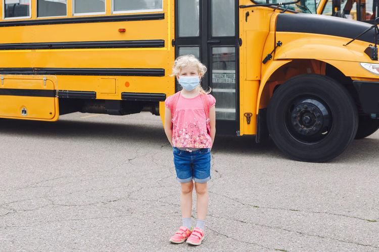 Full length portrait of a girl standing on bus
