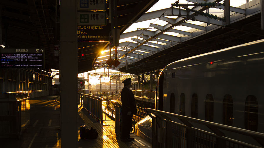 Conductor standing by train at railroad station platform