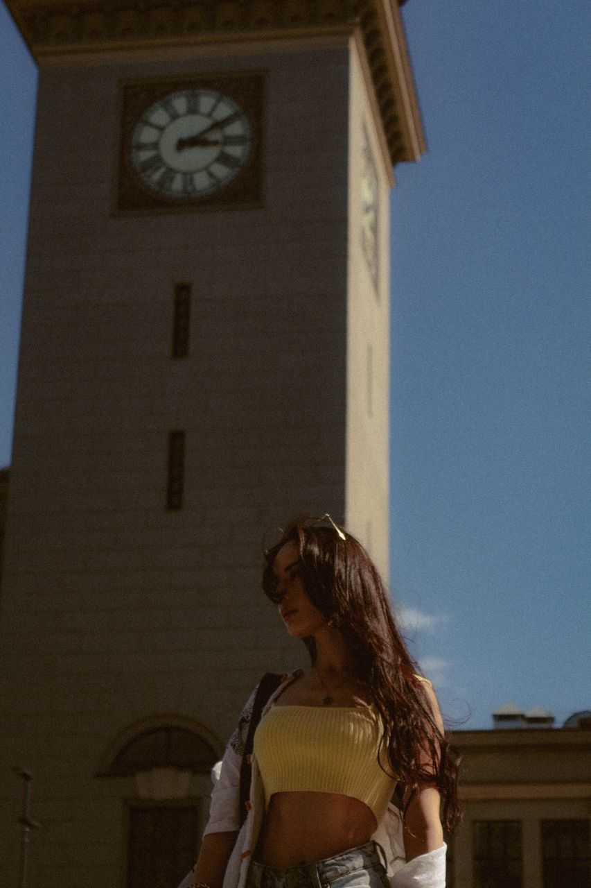 LOW ANGLE VIEW OF WOMAN STANDING AGAINST BUILDING AGAINST SKY