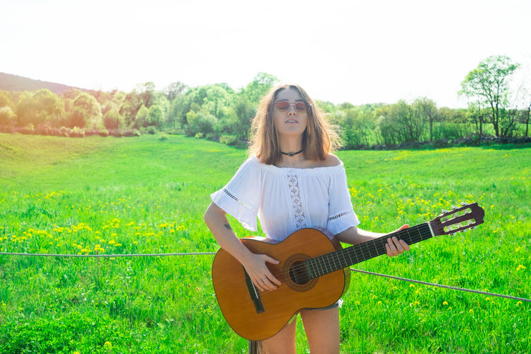 Woman playing guitar while standing on field