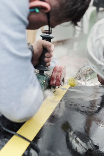 handyman cutting the stone plate with angle grinder and cooling the tool by water jet Cooling  Cutting Industry Man Work Working Angle Grinder Close-up Danger Dust Handyman Holding Occupation Stone Plate Water Jet Work Tool Working Business Stories