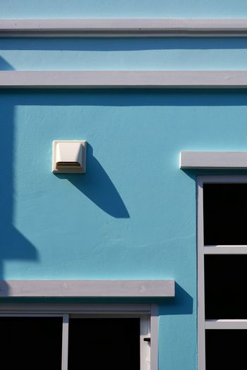 White dryer vent and window frames on surface of pastel blue cement wall background